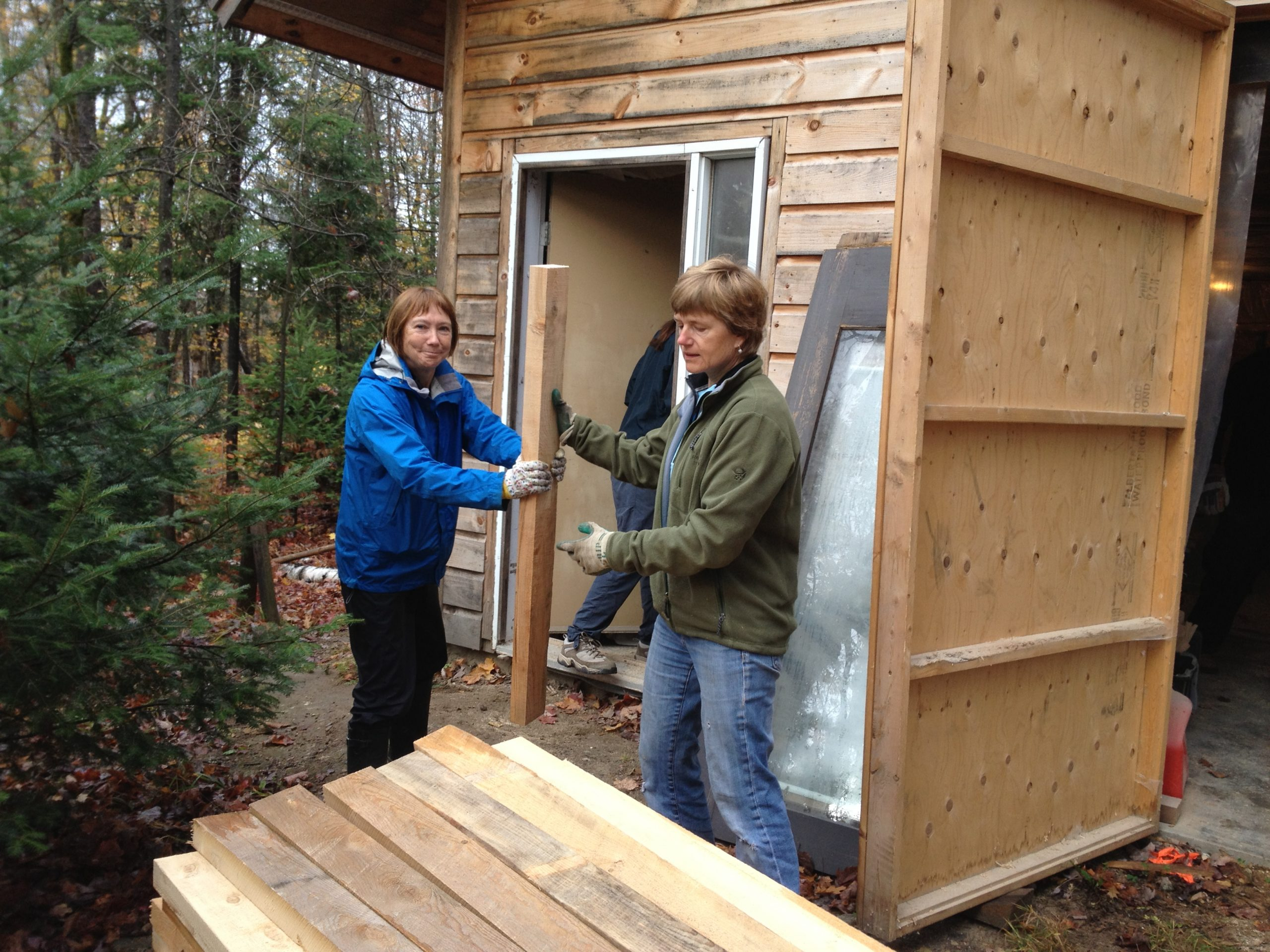 Two people working on building a shed